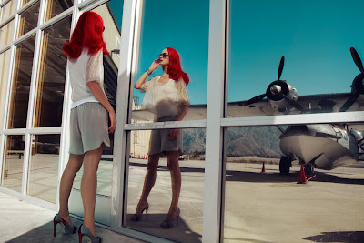 woman looking into reflection, model waiting at airport, fashion photography with airplanes
