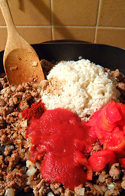 Ground meat, onion, rice, tomato sauce, tomatoes, and spices in frying pan