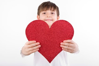 boy holding heart card NAMC montessori community activities valentine's day