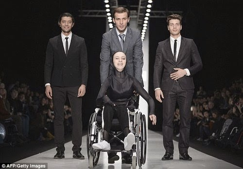 three men and one woman in a fashion show pose, woman is in wheelchair, men standing behind her