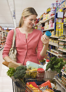 woman reading food label while grocery shopping