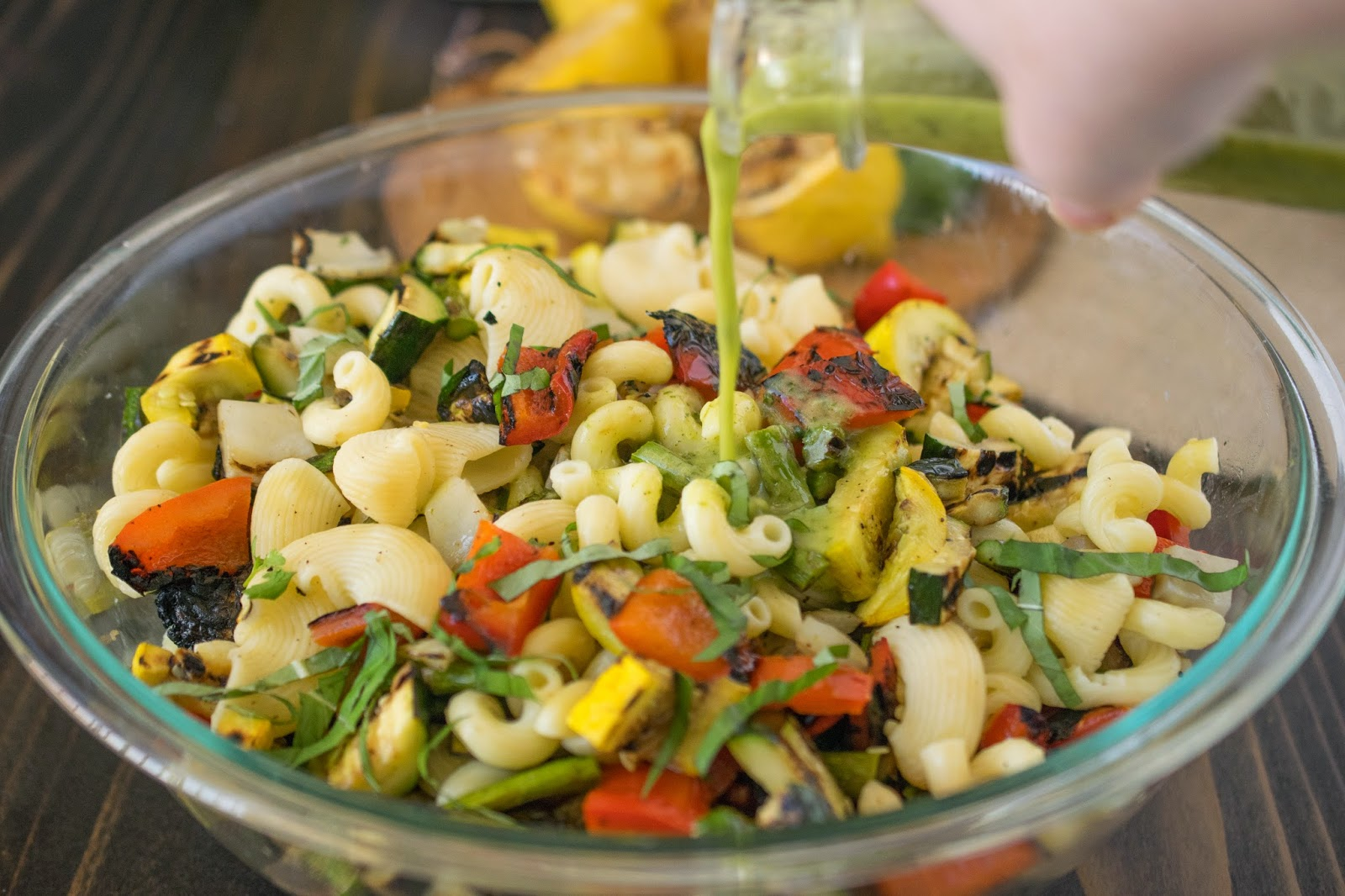 Grilled Spring vegetable pasta salad dressing being poured over the salad in a large glass bowl