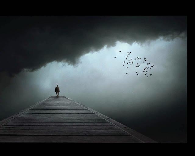 Imagen de un hombre solitario caminando a lo lejos mientras una bandada de aves vuelan en un cielo oscuro y lleno de grises nubes.