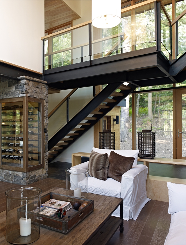 Photo of steel staircase and the gallery above the living room inside of the forest house