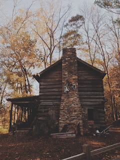 side view of a two-story log cabin with front porch and stone chimney in fall woods