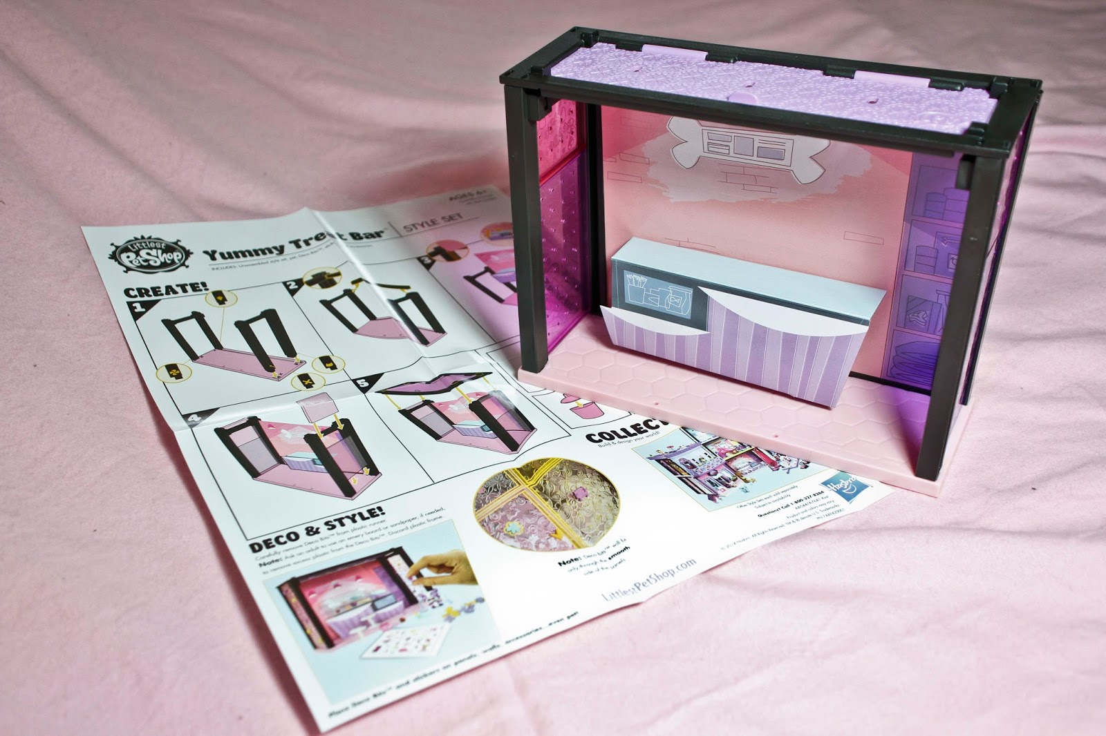 fully assembled littlest pet shop yummy treats bar with the illustrated instructions next to it'