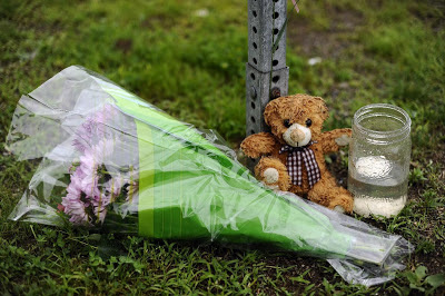 Teddy bear, flowers left in rain in remembrance of Sandy Hook victims