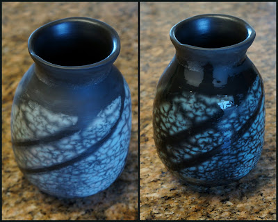 Naked raku pottery - a turquoise vase with black stripe pattern - showing effects of water on the color.