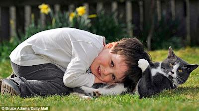 Garoto autista, Fraser Booth, brinca com seu gato Billy, no jardim