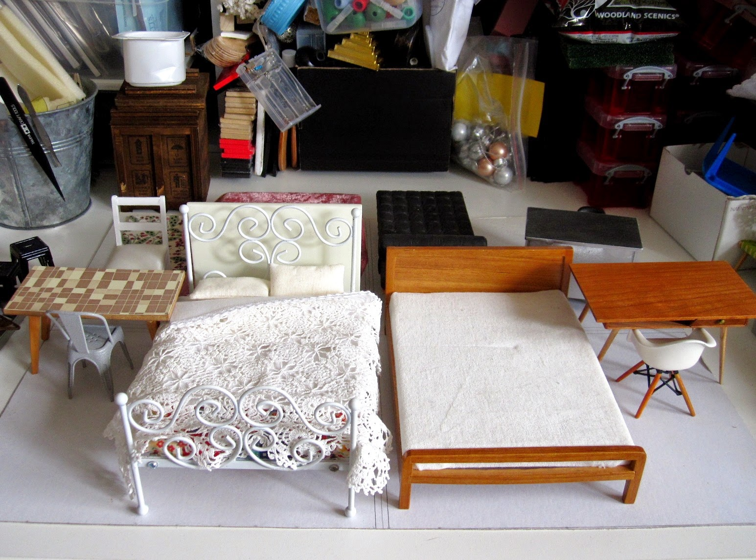 Four sets of modern dolls' house miniature furniture in different styles arranged in room settings on a piece of cardboard.
