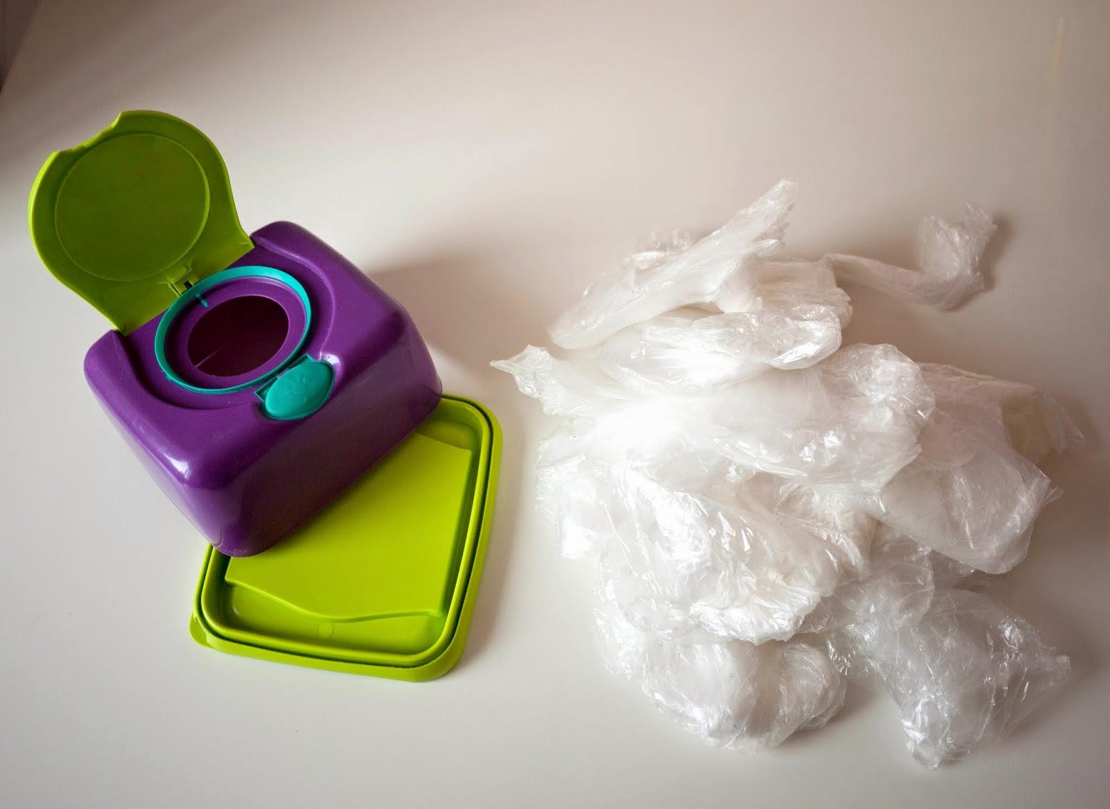 Caja dispensadora de toallitas vacía y un montón de bolsas de plástico pequeñas