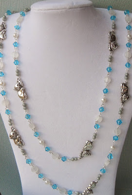 Long blue and clear glass bead necklace with silver cats.