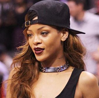 Rihanna dağınık ve uzun saçlarının üstüne ters olacak şekilde siyah beyzbol şapkası takmıştır.