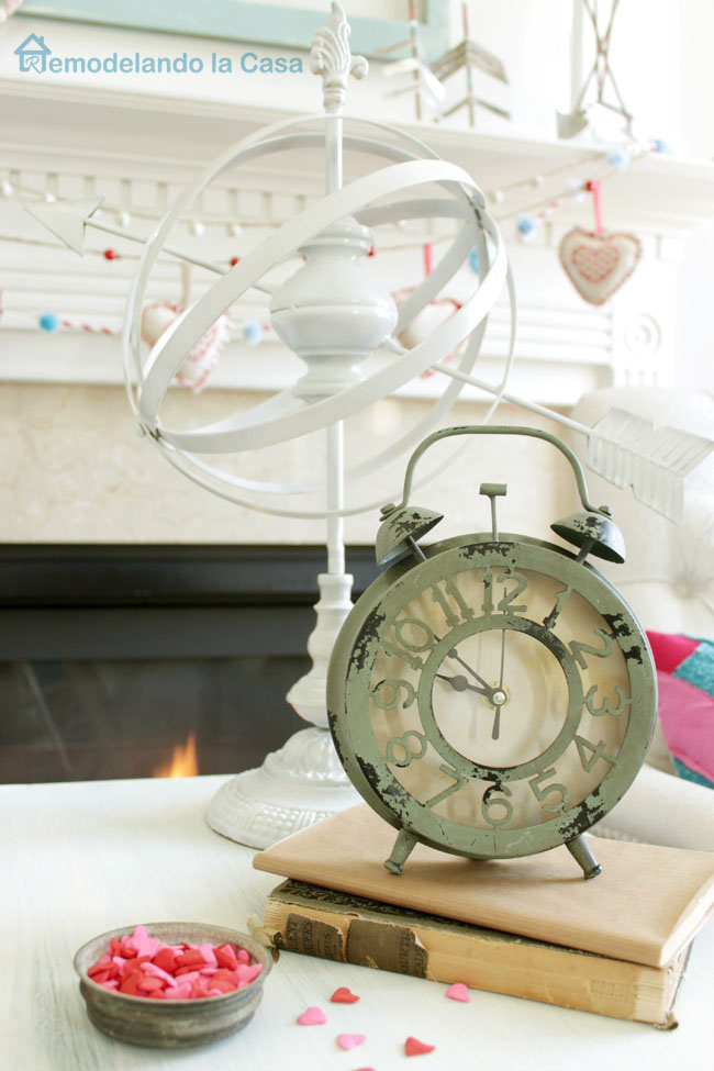 rustic clock and armillary sphere adorning a Valentines mantel