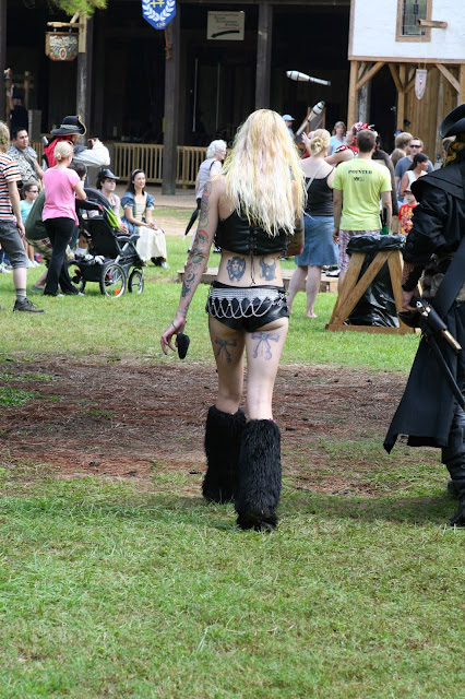 A slim blond woman wears tiny shorts sporting lots of tattoos