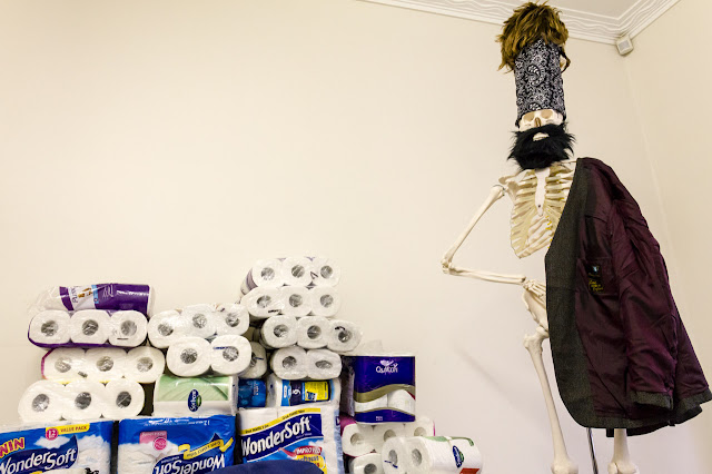 toilet rolls with a skeleton standing next to them