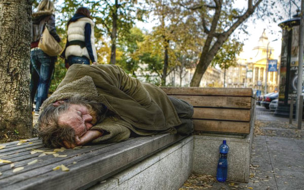 a homeless man sleeping on a park bench as young people pass by