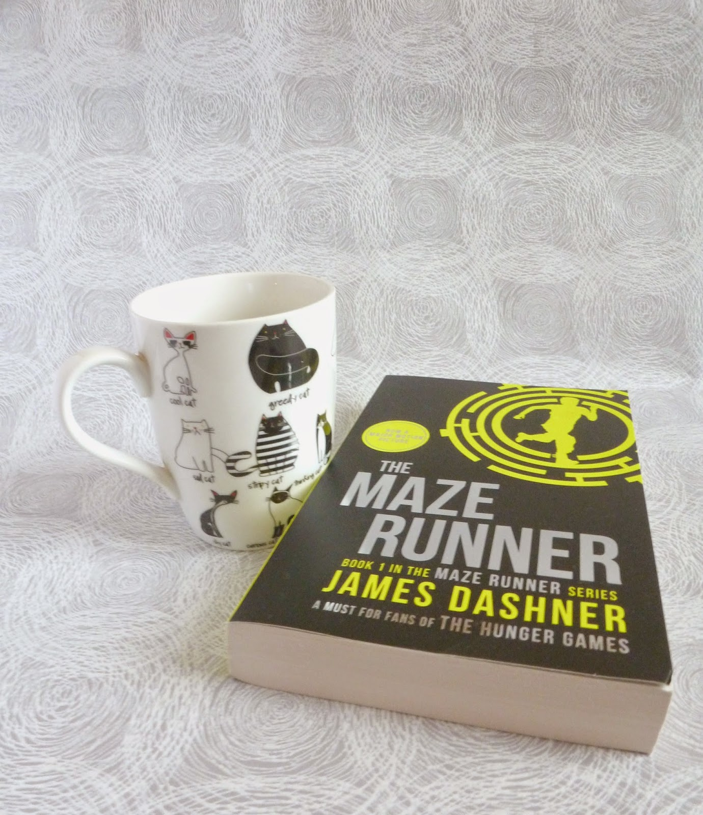 cup of tea in a cat mug and The Maze Runner book by James Dashner