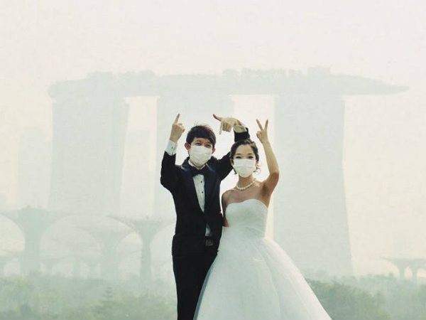 A wedding couple braves the haze to take their photos.