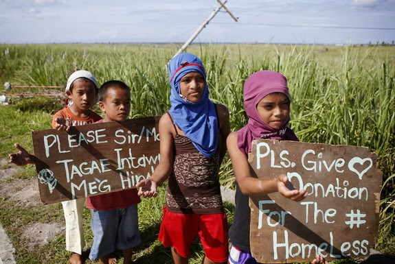 Typhoon Haiyan victims ask for donation from motorists along a highway going to Maya port, Cebu