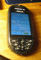 [Image: A Magellan eXplorist XL GPS receiver with a rubber case. It shows the location 50°34.526N, 024°42.434E, elevation 0m, accuracy ---m, Date/Time 31 JAN 13 18:50:53, Trip Odometer 0065.5m.]
