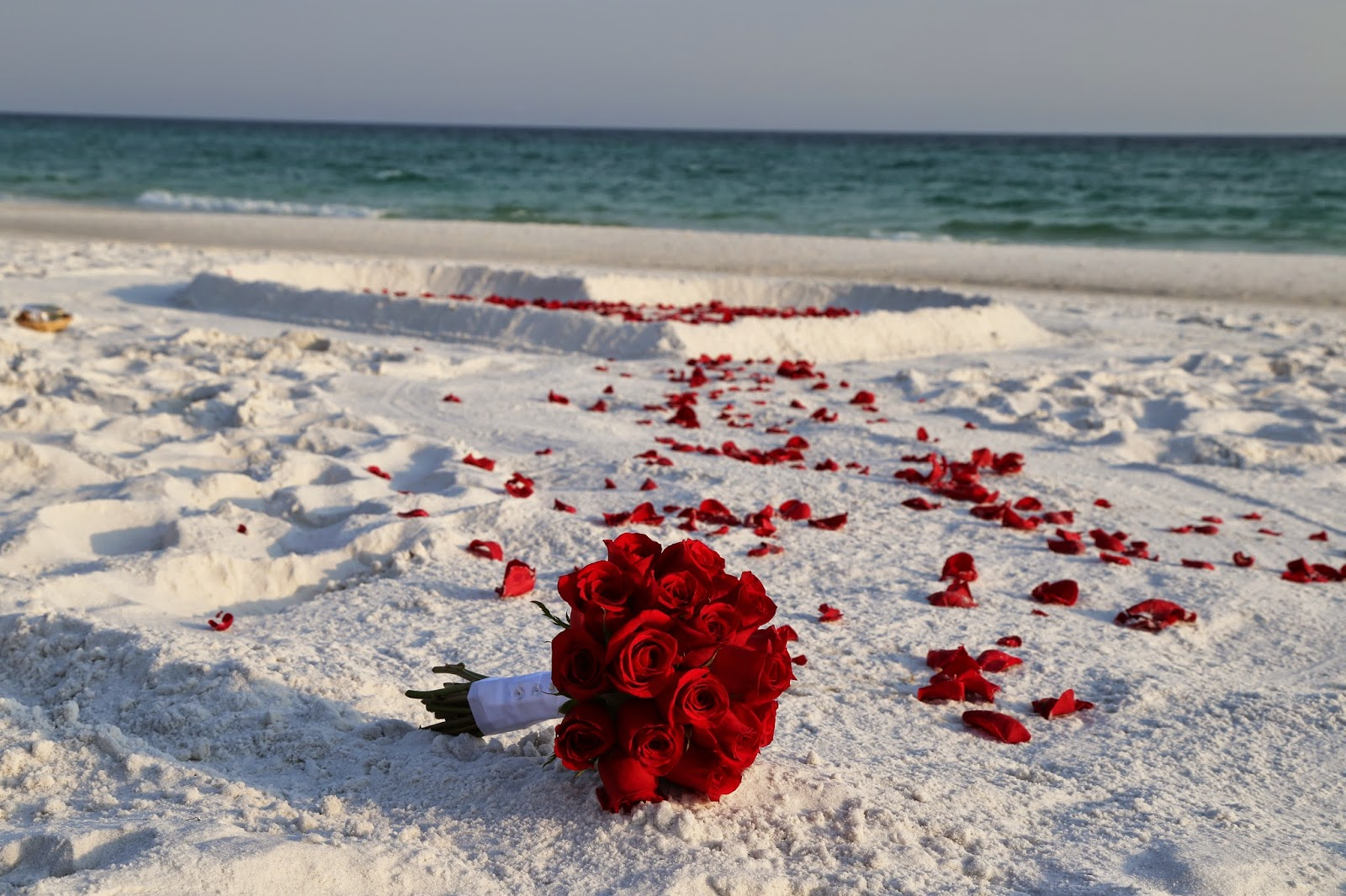 heart in the sand with rose petals and red rose bouquet for beach wedding in Destin, Florida
