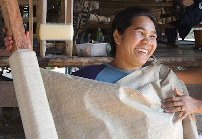 Thai artisan displaying organic silk fabric