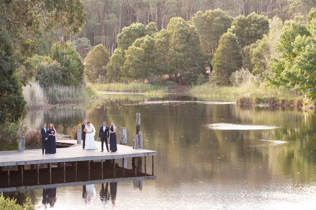 Photo showing bridal party on a pier by a lake in an Australian bush setting