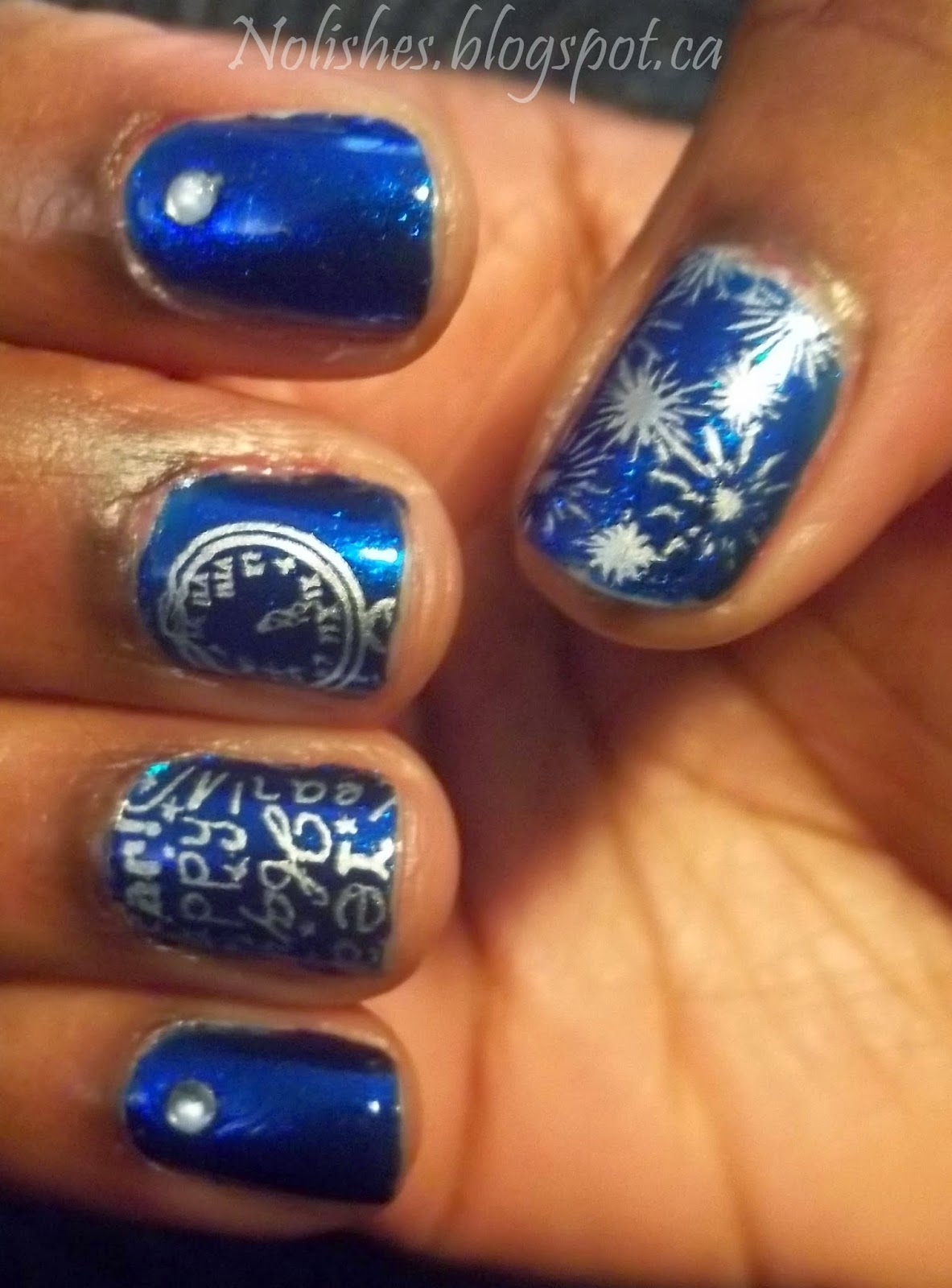 New Year's themed nail stamping manicure featuring a deep blue shimmery fleck polish stamped with New year's themed images in silver.