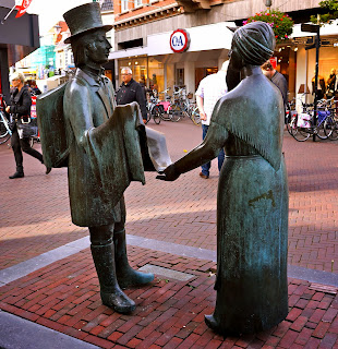 Statue of a peddler selling a piece of cloth to a peasant woman in Sneek.