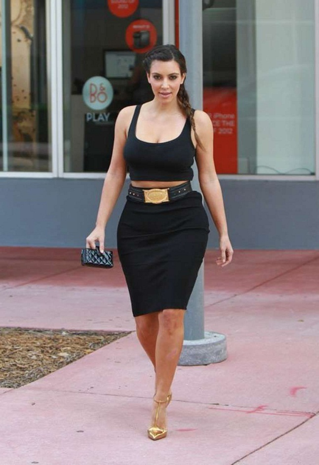 Kim Kardashian flashes her stomach in a tight crop top and pencil skirt