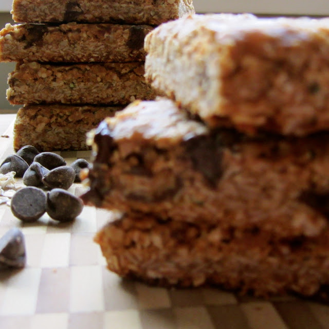 pile of baked honey oat bars on a wooden cutting board. chocolate chips and oats in background