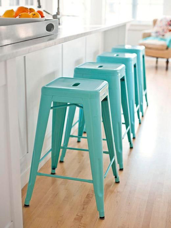In line turquoise tolix counter stools add a fresh note in an otherwise neutral kitchen.