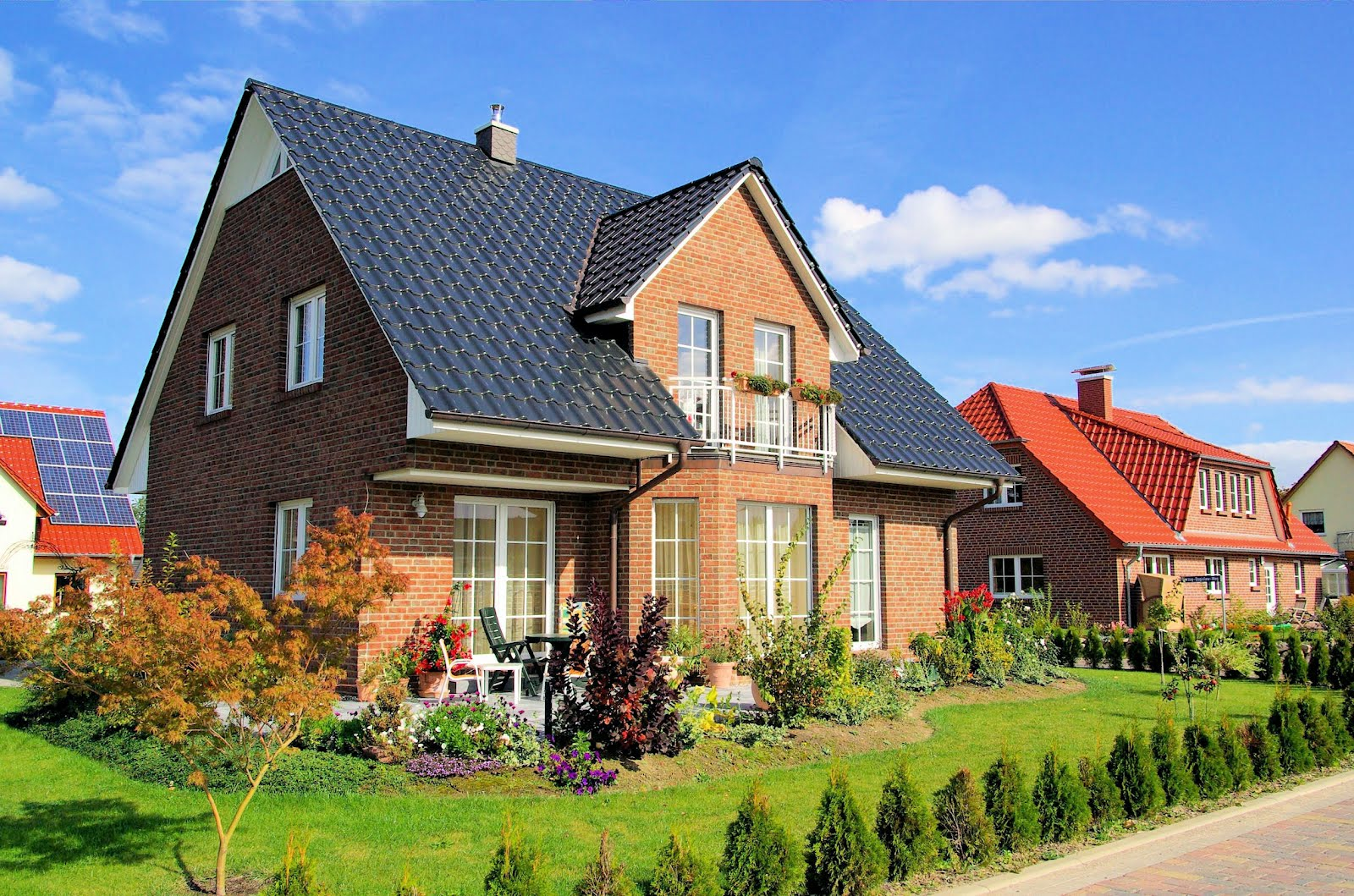 Casas bonitas y jardines con flores en el cielo azul for Fotos de jardines de casas modernas