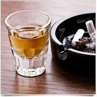 A hard drink and a cigarette tray