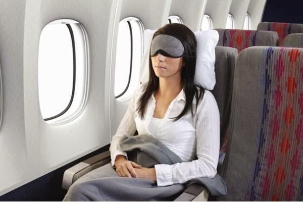 woman sleeping in plane by wearing eye mask