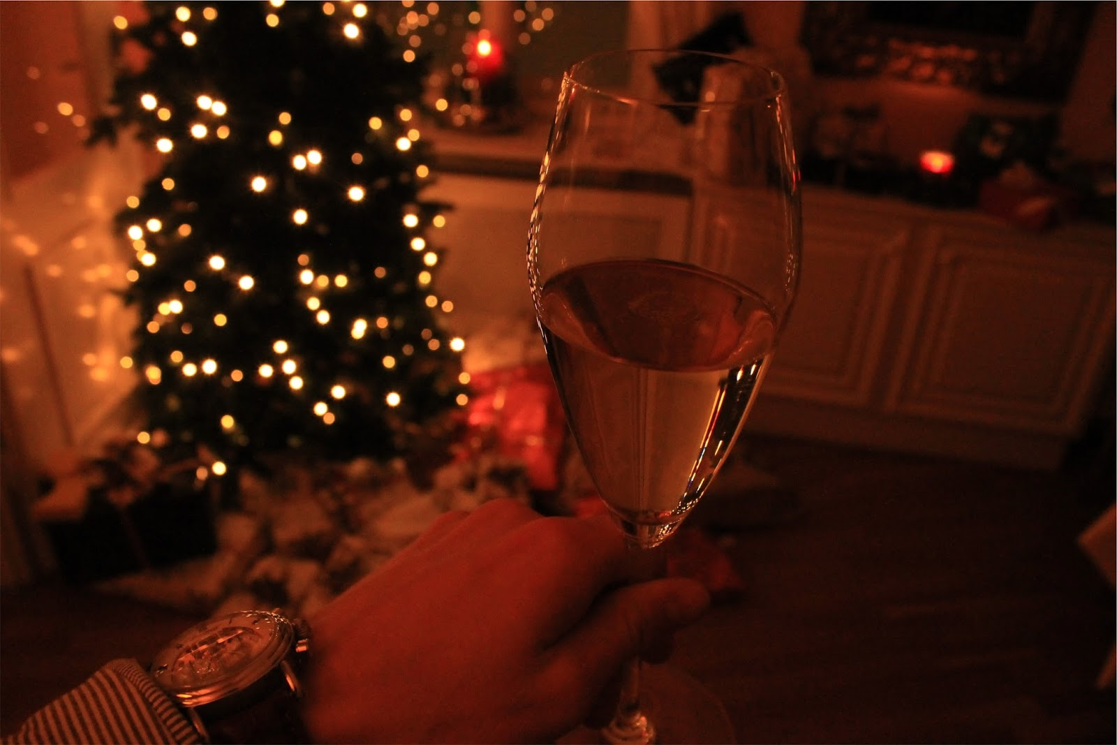 Man drinking wine by a Christmas Tree-easier cooking this Christmas - motherdistracted.co.uk
