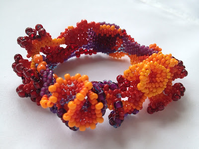 Freeform peyote bracelet shading from yellow-orange to violet through the warm side of the color wheel