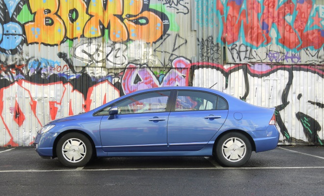 Honda Civic Hybrid in front of a wall of grafitti