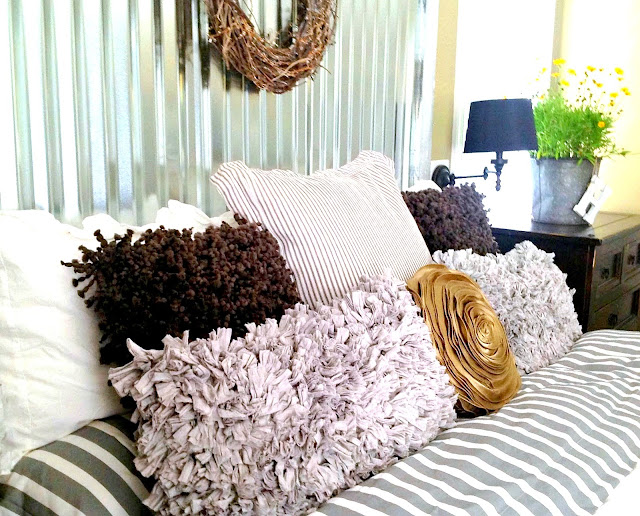 Gorgeous layered pillows, part of a fantabulous industrial metal siding headboard by Down To Earth Style, featured on I Love that Junk