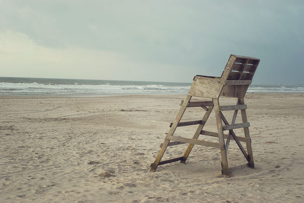 a scene with a lifeguard's chair looking out towards the sea