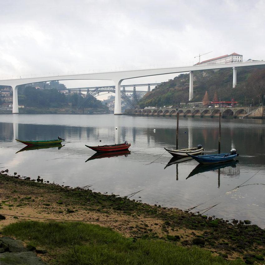 Paisagem do rio Douro com barcos na margem, em primeiro plano e as três pontes ao longe. Céu nublado e atmosfera com neblina
