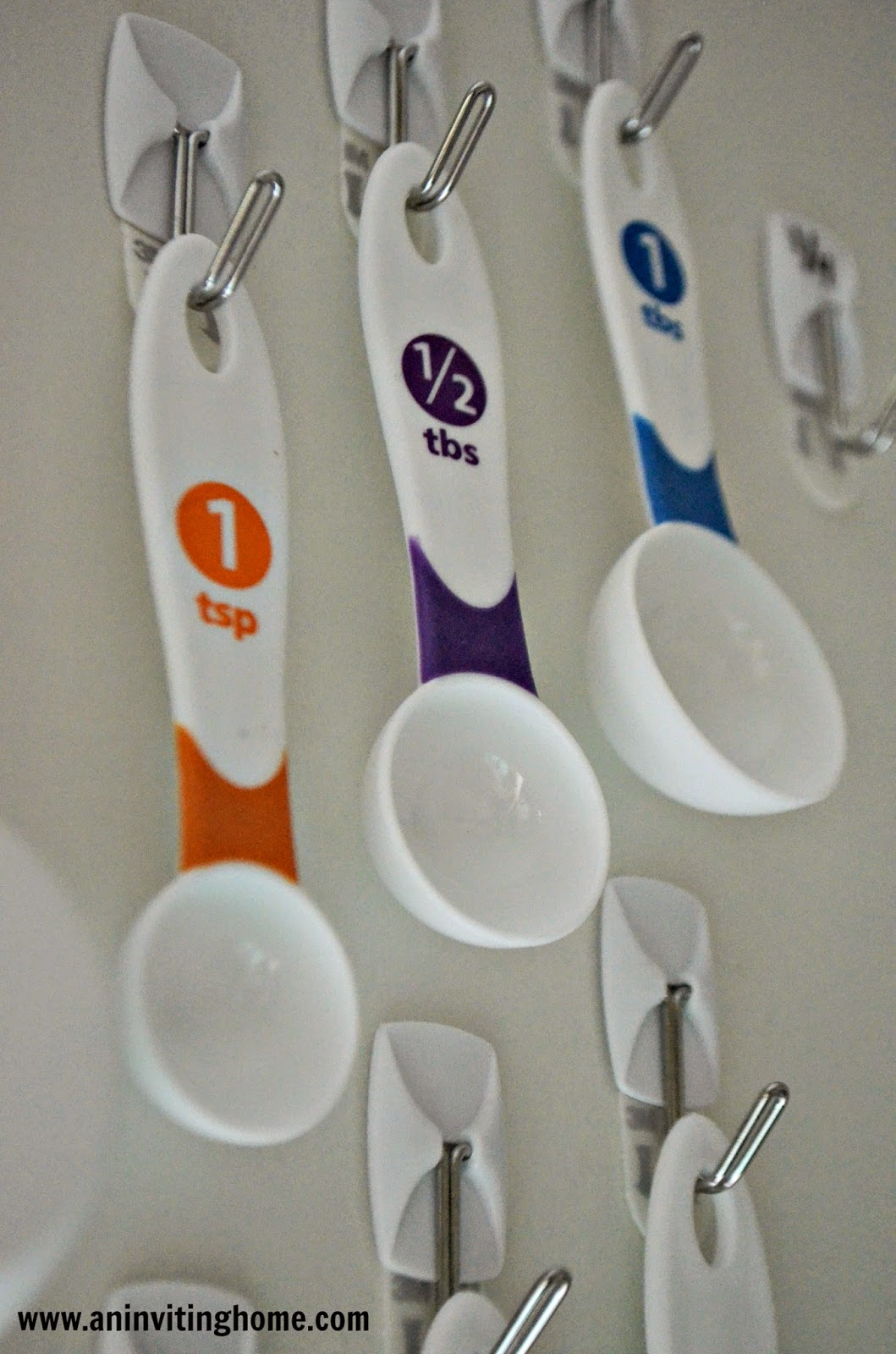 hanging measuring spoons on the back of a cupboard door