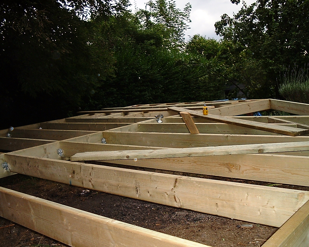 to build a timber base use treated joists insert pads to carry the timbers at spacing which will not allow joists to bend fix the joists together building a garden office