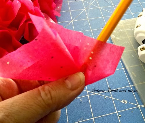 showing how to wrap tissue around pencil