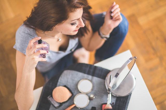 kobieta aplikująca perfumy