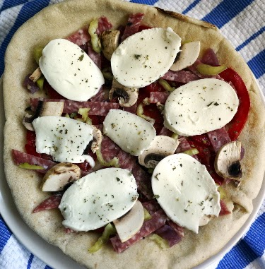 pita pizza cooked in toaster oven with mozzarella, salami, eggplant pickle, heirloom tomato, and hot pepper