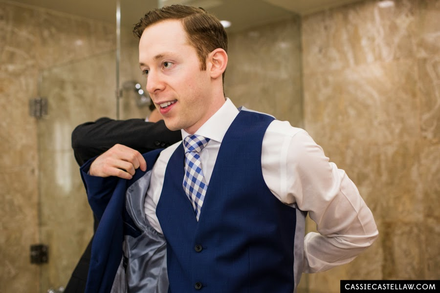Best man helping groom put on his jacket. Custom blue suit and blue checked tie. NYC Lifestyle wedding photography by Cassie Castellaw. www.cassiecastellaw.com