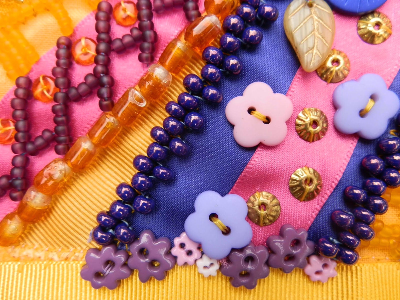 Detail showing rows of purple beads and small pink and purple flower shaped buttons