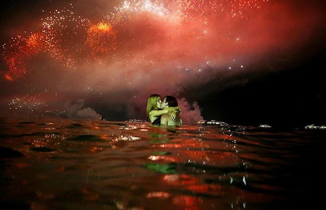 Влюбленные под огнями фейерверков в воде у пляжа Копакабана в Рио-де-Жанейро.